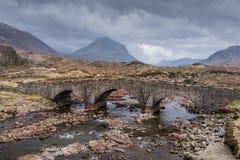 Sligachan Old Bridge in the Isle of Skye, Scotland. Sligachan Old Arched Bridge under the cloudy sky, located in the Isle of Skye, Scotland UK Stock Image