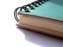Slightly battered green spiral bound notebook. On white background Royalty Free Stock Photos
