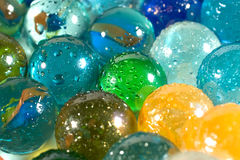 Slightly blurred colorful marbles. (with drops of water) as a background Royalty Free Stock Images