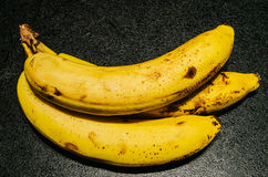 Slightly browned bananas on textured black background Stock Photography