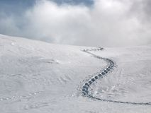 Slightly Lost. A single trail of footprints in deep snow stock photography