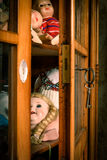 Slightly opened glass cabinet with antique dolls. Stock Photo Stock Image