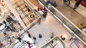 Slightly panned up high shot of people shopping. Detailed view of people walking on cross section of second floor stock video footage