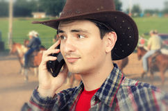 Slightly perplexed cowboy talking on phone Stock Photography