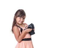 Slightly skewed  little girl is holding SLR camera. Smiling long hair little girl is holding SLR camera. The girl is slightly skewed and is looking at the camera Stock Photo