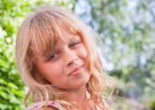 Slightly smiling little blond girl portrait Stock Photos