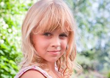 Slightly smiling little blond girl portrait Royalty Free Stock Photo