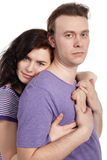 Slightly smiling woman embraces man from behind Stock Images