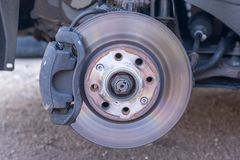 Slightly worn brake disc and wheel hub of a car in detail stock photo