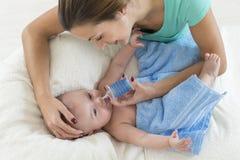 Slijm van de moeder het schoonmakende neus van aanbiddelijke baby met een neusaspirator stock foto