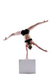 Slim acrobat balancing on cube in studio Royalty Free Stock Photography