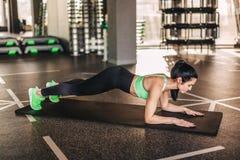 Slim adult sportswoman in plank on mat stock photo