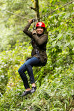 Slim Afro Girl On Zip Line. Adult Slim Afro Woman On Zip Line In Ecuadorian Rainforest Nearby Banos De Agua Santa royalty free stock images
