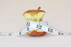 Slim apple. An half eaten apple with a measuring tape around it Stock Photography
