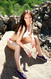Slim athlete girl posing on the rocks Stock Photo