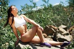Slim athlete girl posing on the rocks Stock Photo
