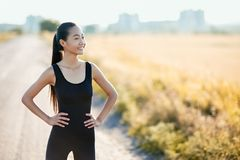 Slim athletic Asian woman resting on rural road in sunny day Royalty Free Stock Photo