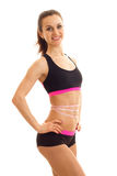 Slim athletic girl with the measuring tape at the waist keeps his hand on the side and smiling Royalty Free Stock Image