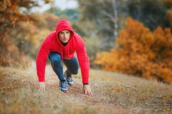 A slim  athletic jogger man at the start preparing to run on the Royalty Free Stock Images