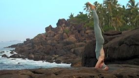 Woman does head stand on flat stone near ocean slow motion. Slim athletic woman does head stand on flat stone near rolling ocean waves and palm trees low angle stock footage