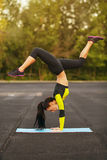 Slim athletic woman doing exercise handstand in the stadium, sporty girl workout, outdoors Stock Photography
