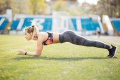 Slim athletic woman doing planking exercise in the stadium on green grass of football field, sporty girl workout, outdoors. Slim athletic woman doing planking stock photo