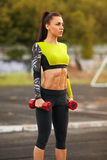 Slim athletic woman with dumbbells in the stadium. Sporty sexy girl with flat belly workout, outdoors.  Royalty Free Stock Images