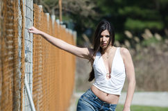 Slim athletic woman standing against fencing wire Stock Photos