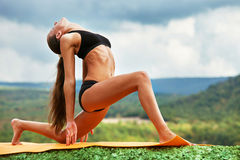 Slim athletic woman in warrior yoga pose Stock Photography