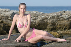 Slim attractive blonde on beach wear bikini. Slim attractive blonde with ponytail wearing bikini and lie on the sea rock. Full length horizontal portrait. Sea as Stock Photo