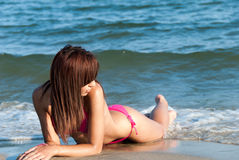 Slim attractive body in pink bikini. Young woman with slim attractive body wearing pink bikini lie on wet sand, looking back, sea as background. Full length Royalty Free Stock Photography