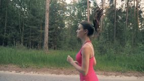 Slim attractive lady running along the alley. Healthy lifestyle concept. stock video footage