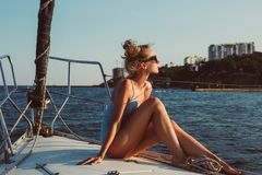 Profile portrait of young woman is sitting on the deck of boat royalty free stock images