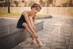 Slim ballerina in a blackdress putting on pointe shoes. outdoor Royalty Free Stock Photos