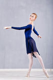 Slim ballerina in a blue dress dancing. Royalty Free Stock Images
