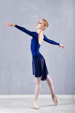 Slim ballerina in a blue dress dancing. Royalty Free Stock Photo