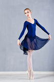 Slim ballerina in a blue dress dancing. Stock Photo