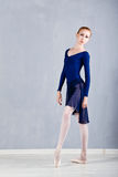 Slim ballerina in a blue dress dancing. Stock Photography