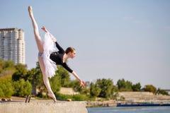Slim ballerina in tutu dancing on promenade. Arabesque. Young slim ballerina in tutu dancing on the pier of the city. Summer day. The concept contemporary ballet Stock Image