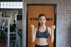 Slim beautiful asian woman posture standing and lifting up her arms and exercises muscle at gym,Positive thinking stock images