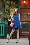 Slim beautiful girl dressed in a blue summer dress holding a pink bag is standing in a city street on a warm day royalty free stock photography