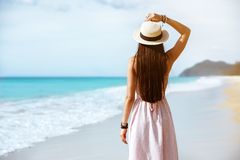 Slim lady in dress and hat walks at sea beach royalty free stock images