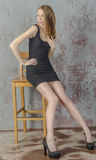 Slim beautiful red-haired girl in a black mini dress with a chair Stock Image