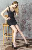 Slim beautiful red-haired girl in a black mini dress with a chair Stock Photography