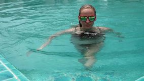 Slim beautiful woman comes into hotels swimming pool and caming out. summer vacation concept.  stock footage