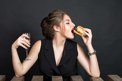 Slim beautiful woman eating a hamburger Stock Photography