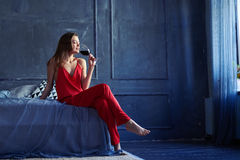 Slim beautiful woman with a glass of wine sitting on the bed. Low angle shot of a slim beautiful woman with a glass of wine sitting on the bed. Girl in a red Stock Images