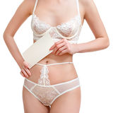 Slim, beautiful woman in lace lingerie holding blank sheet of paper. Body parts, closeup of women half length body in Stock Photography