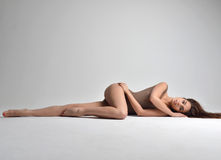 Slim beautiful woman lying on a floor in sexy underwear on grey Stock Images