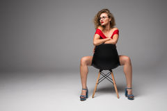 Slim beautiful woman posing on a black chair in sexy underwear on gray background Royalty Free Stock Photos